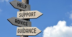 A sign post with the signs, Help, Support, Advice, Guidance posted on it